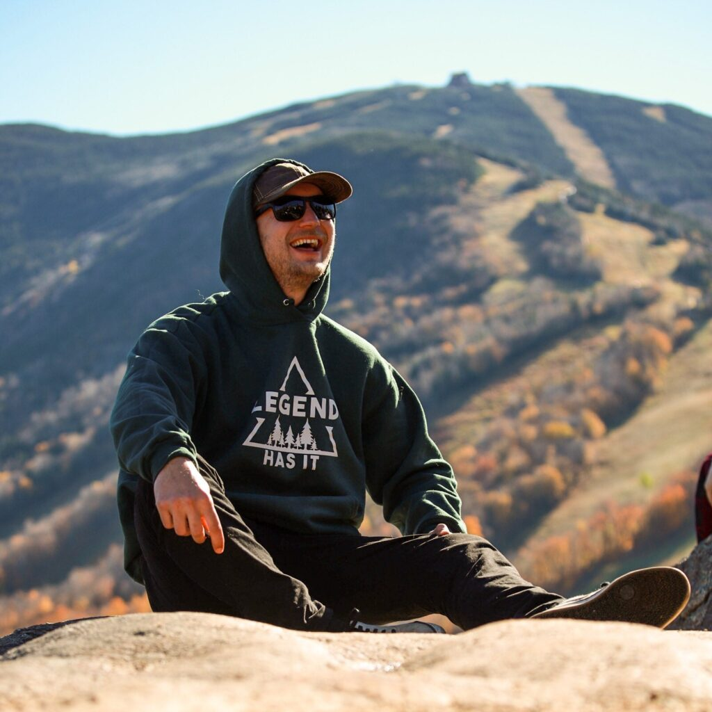 Aaron sits on a rock with mountains in the background. He is smiling widely.