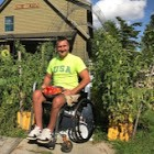 Thomas sits in his wheelchair, surrounded in green plants, holding a basket of tomatoes.