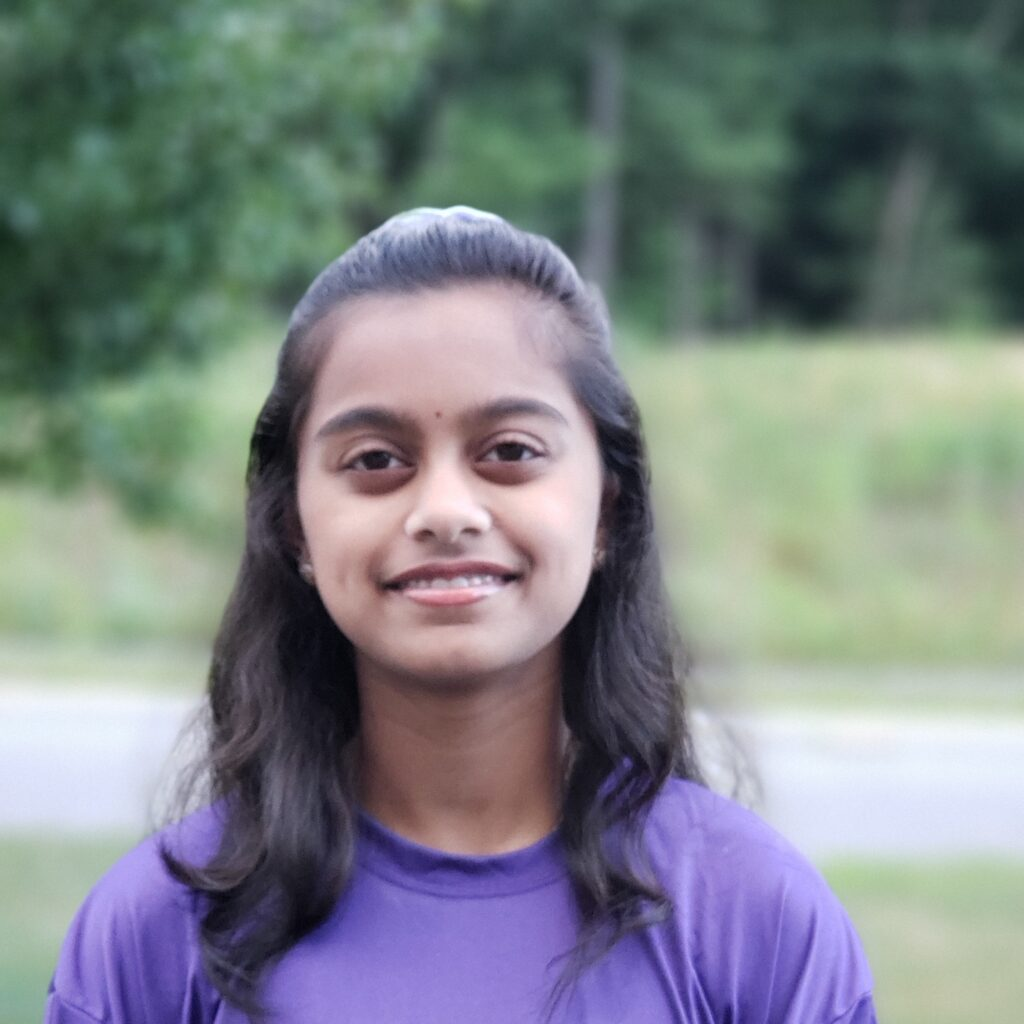 Likhita smiles at the camera, wearing a purple shirt.