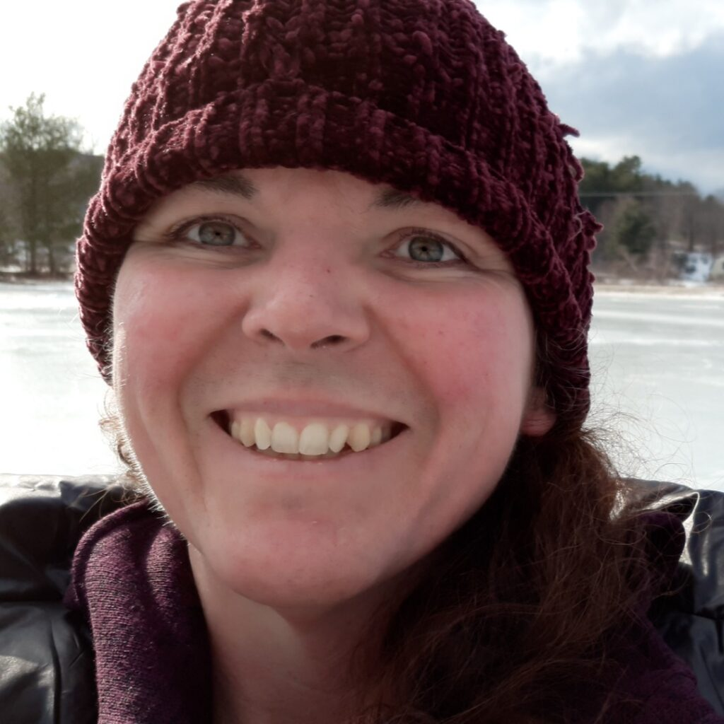 Pamela smiles widely at the camera, wearing a hat and coat, surrounded in a snowy field.